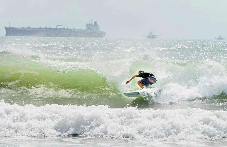 Un surfista se desplaza a orillas de la isla del Padre Sur el viernes 24 de julio de 2020 en medio de un mar picado debido a la tormenta tropical Hanna. Photo: Miguel Roberts /Associated Press / The Brownsville Herald