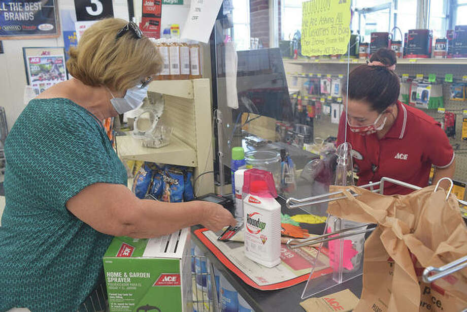 Joann Jones of Franklin wears a mask Friday as she purchases items at Ace Hardware Store in Jacksonville. A screen separates Jones from Ace employee Kaylee Bettis as Bettis works the register. Photo: Marco Cartolano | Journal-Courier