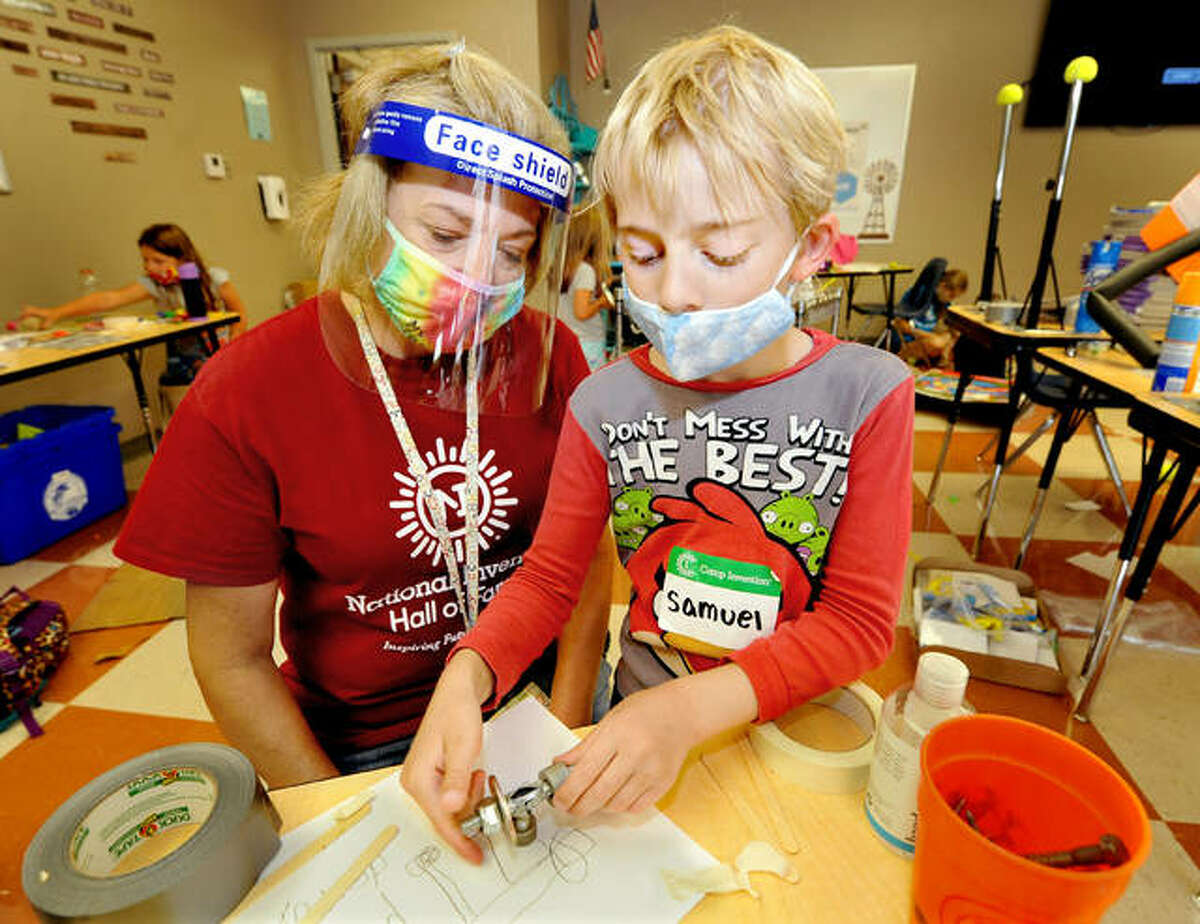 """Samuel Moore, 8, of St. Jacob, right, works on his prototype of what he calls a """"planet killer"""" with the help of kindergarten teacher Sheri Hodapp during Camp Invention at St. John Neumann Catholic School in Maryville Wednesday."""