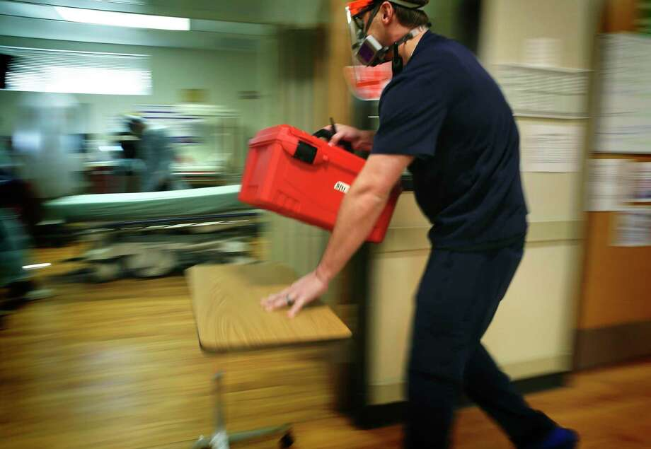 Corey Mokry, a nursing director in the emergency room of Christus Santa Rosa, rushes a medical kit to a room being prepared for a COVID-19 patient arriving by ambulance on July, 20, 2020. / ©2020 San Antonio Express-News