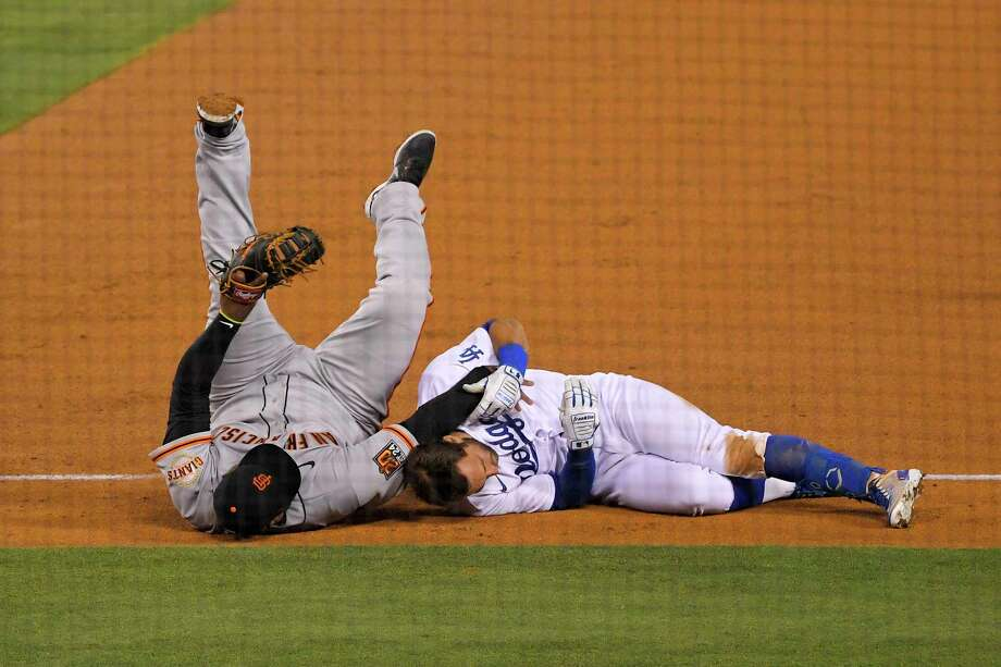 San Francisco Giants third baseman Pablo Sandoval, left, and Los Angeles Dodgers' Chris Taylor fall to the ground after they collided while Taylor was running to first on a single during the fifth inning of a baseball game Friday, July 24, 2020, in Los Angeles. Photo: Mark J. Terrill, AP / Copyright 2020 The Associated Press. All rights reserved.
