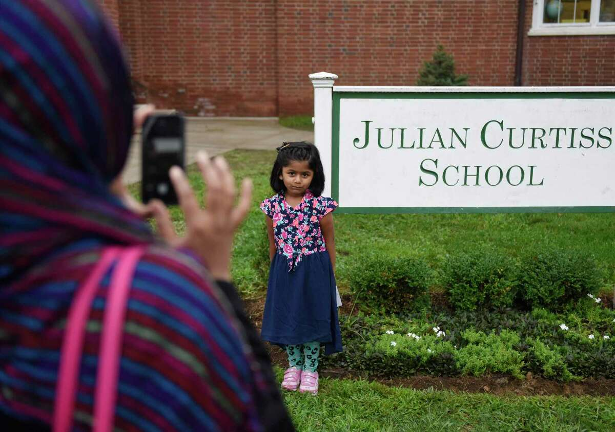 Aysha Rajpud photographs her daughter, kindergartner Amama Rajpud, on the first day of school at Julian Curtiss School in Greenwich, Conn. Thursday, Sept. 1, 2016.