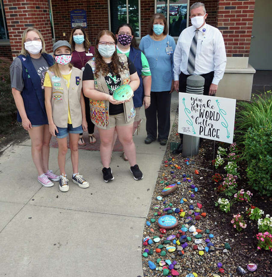 Members of Girl Scouts Service Unit 101 delivered more than 100 hand-painted rocks (see on the ground) to Alton Memorial Hospital on July 8, placing the rocks near the Duncan Wing entrance. Left to right, from the Girl Scouts are Karie Preston, Elisabeth Preston, KayLee Melton and Jennifer Melton. The Prestons are with Troop 792 out of St. Ambrose Parish, and Karie is the recording secretary for Service Unit 101. The Meltons are with Troop 130 out of Wood River, and Jen is the Service Unit manager. Back row, left is Kristen Ryrie, AMH development officer, and at right are AMH vice presidents Debbie Turpin and Brad Goacher.