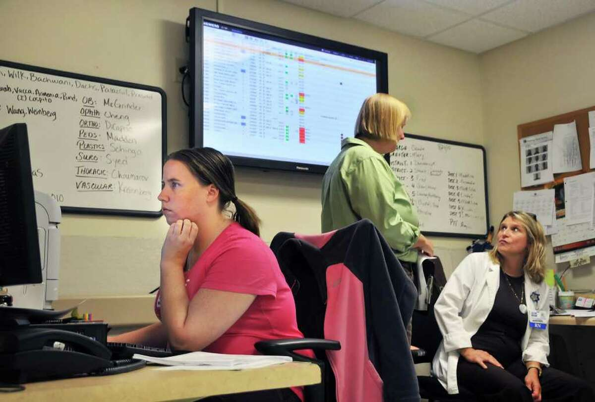 Stephanie Brown, left, reviews patient's charts as crisis evaluator Laurie Pelham and RN Fran DiGenova, at right, confer under one of the monitors of the new ER board at Ellis Hospital. (John Carl D'Annibale / Times Union)