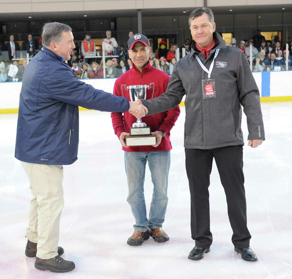At right, Greenwich coach Chris Rurak shakes hands with Darien coach Mac Budd prior to the tip off of the 3rd Ice Hockey Winter Classic at the Greenwich Skating Club in December.