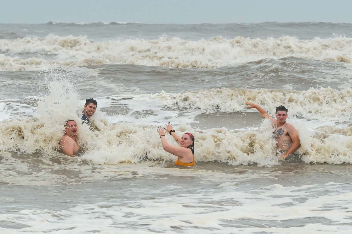 Four people enjoy some time in the high surf at Crystal Beach, Texas, brought on by Hurricane Hanna. Even though Hurricane Hanna made landfall several hundred miles south of the Bolivar Peninsula, the storm still had an effect on the area. Photo made on July 25, 2020. Fran Ruchalski/The Enterprise