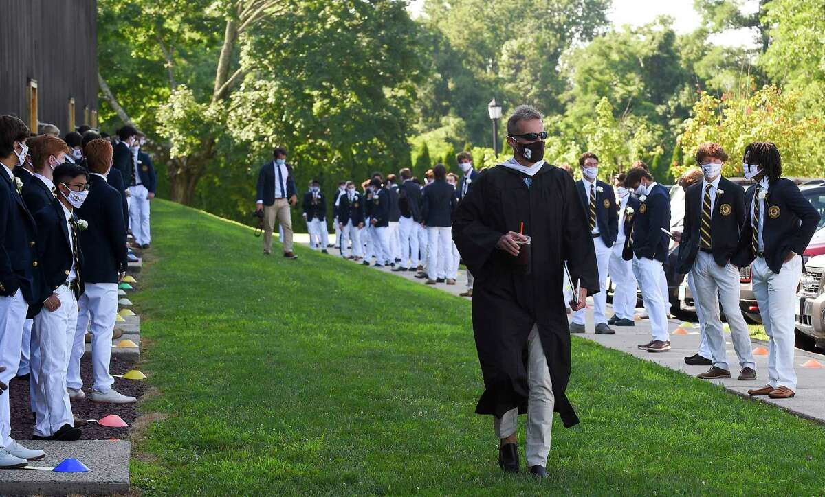 Brunswick School Head of School Thomas Philip chats with students as he makes his way to start the One hundred and Eighteenth Commencement ceremony on Cosby Field July 25, 2020 at the school in Greenwich, Connecticut. The faculty also missed seeing the memorable Class of 2020 after the students moved to remote learning in mid-March.
