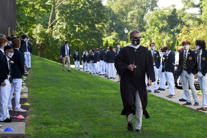 Brunswick School Head of School Thomas Philip wears a mask, and so do the students, as he makes his way to start the ceremony on Cosby Field July 25, 2020 at the school in Greenwich, Connecticut.