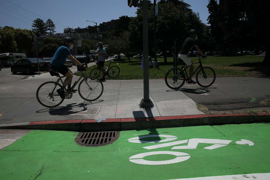 Cyclists bike near the new bike lane at Fell and Baker Streets in San Francisco on Saturday. Photo: Yalonda M. James / The Chronicle