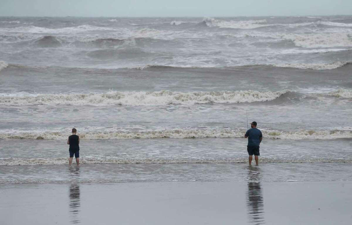 Two people try to fish while at the beach on Saturday, July 25, 2020, in Galveston, Texas. Outer bands of Hurricane Hanna are affecting the Houston and Galveston areas.