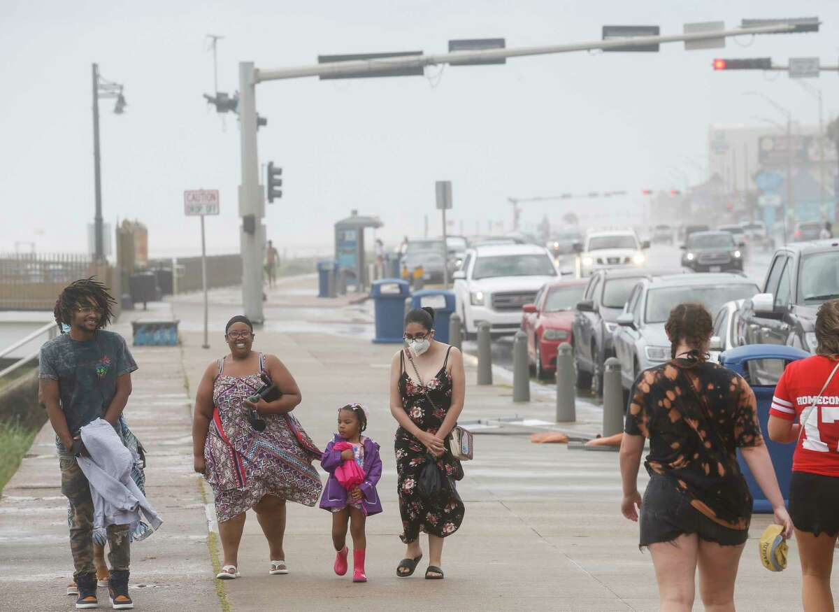 A group of people walk along Seawall Boulevard as heavy winds arrive on Saturday, July 25, 2020, in Galveston, Texas. Outer bands of Hurricane Hanna are affecting the Houston and Galveston areas.
