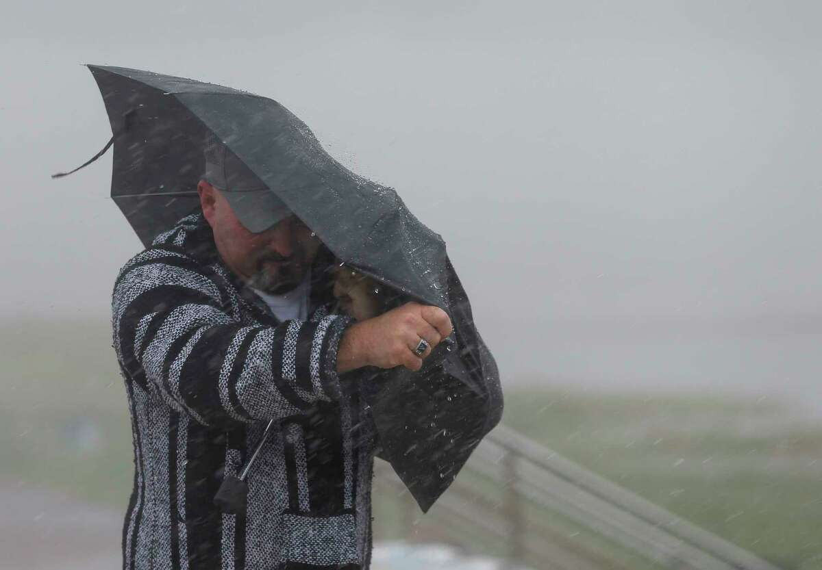 A man holds the front on his umbrella as he fights heavy rain and wind on Seawall Boulevard on Saturday, July 25, 2020, in Galveston, Texas. Outer bands of Hurricane Hanna are affecting the Houston and Galveston areas.