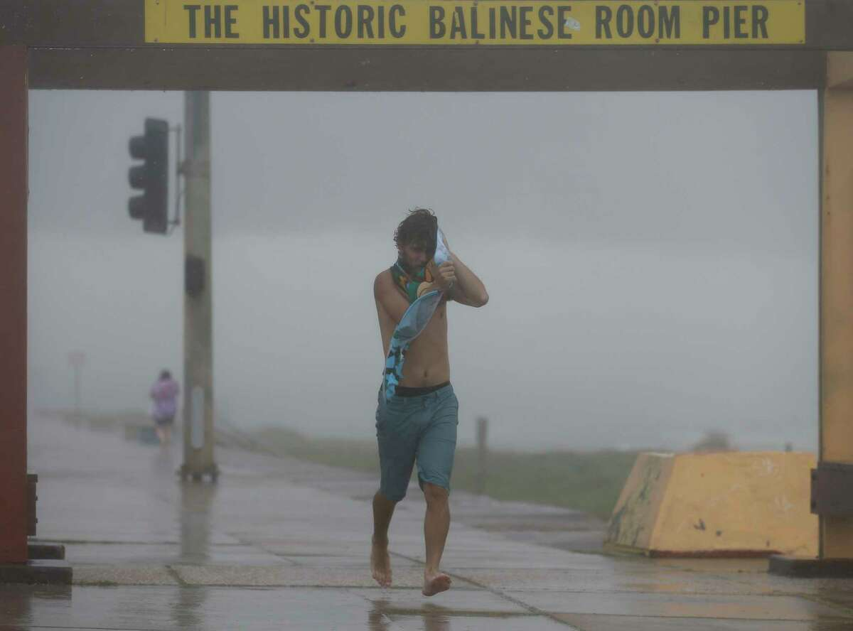 Devin Brown uses a towel to cover his face from heavy rain and wind on Seawall Boulevard on Saturday, July 25, 2020, in Galveston, Texas. Outer bands of Hurricane Hanna are affecting the Houston and Galveston areas.