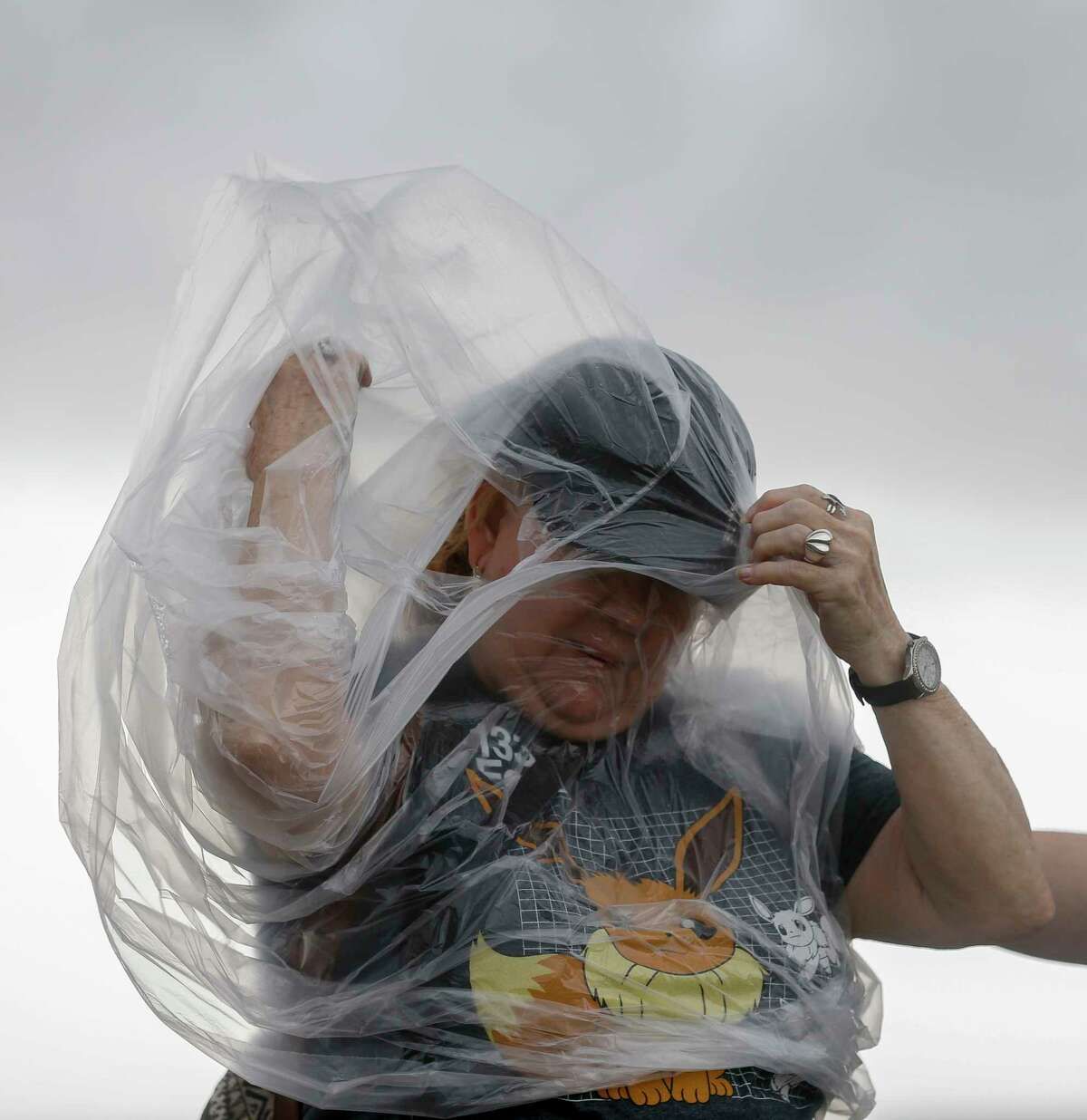 Susan Choate fights the wind to put on a poncho while taking a quick break from being part of the Pokemon Go Fest, which is virtual this year, along Seawall Boulevard on Saturday, July 25, 2020, in Galveston, Texas. Outer bands of Hurricane Hanna are affecting the Houston and Galveston areas.
