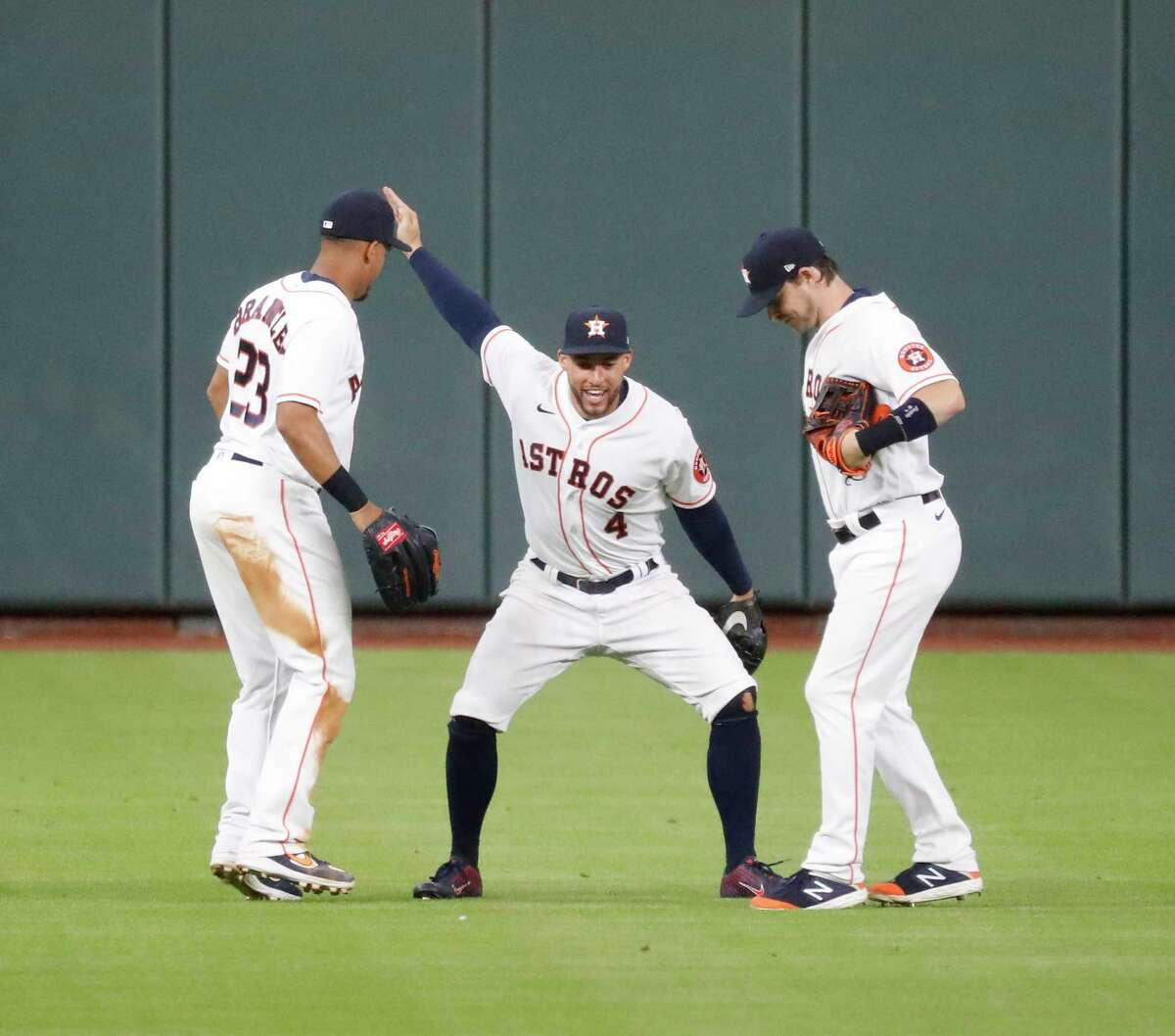 Houston Astros center fielder George Springer does a silly dance with Michael Brantley and Josh Reddick after the Astros beat the Seattle Mariners 7-2 during an MLB baseball game at Minute Maid Park, Saturday, July 25, 2020, in Houston.