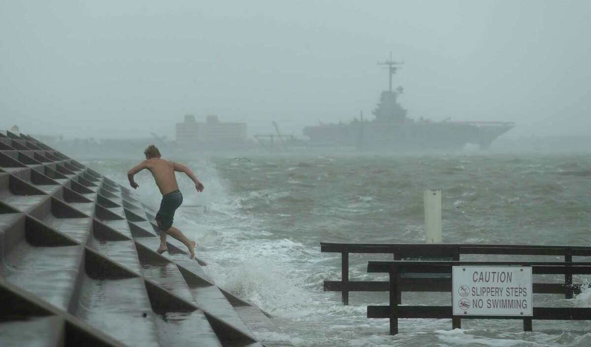 A man jumps from a wave as Hurricane Hanna begins to make landfall, Saturday, July 25, 2020, in Corpus Christi, Texas. The National Hurricane Center said Saturday morning that Hanna's maximum sustained winds had increased and that it was expected to make landfall Saturday afternoon or early evening.(AP Photo/Eric Gay)