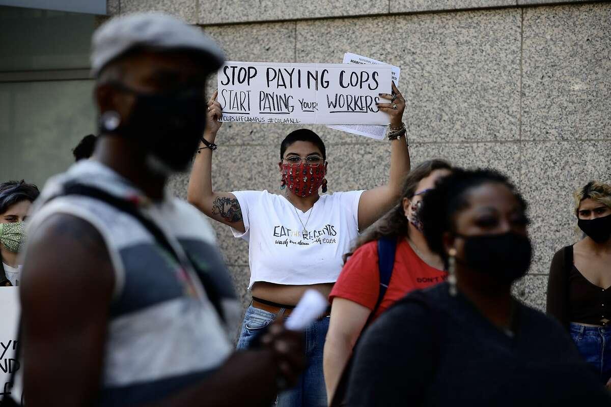 Shreya Deshpande, 23, a UC Davis student, holds a sign that states,