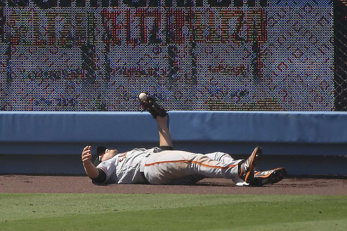 San Francisco Giants left fielder Austin Slater lays on the ground after making a catch on a ball hit by Los Angeles Dodgers' Corey Seager during the sixth inning of a baseball game Saturday, July 25, 2020, in Los Angeles. (AP Photo/Mark J. Terrill)
