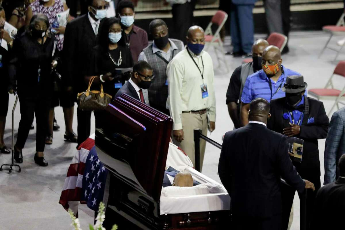 Mourners walk past the casket of the late Rep. John Lewis, D-Ga., during a service celebrating