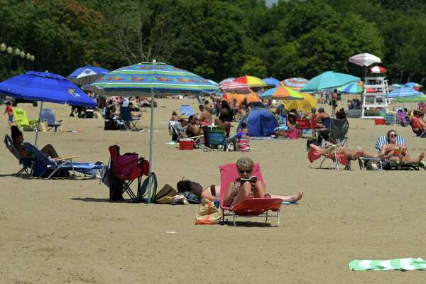 Residents enjoy a sparse Calf Pasture Beach Saturday, July 25, 2020, in Norwalk, Conn. Norwalk and surrounding communities decided to ban nonresidents on weekends from their beaches in an effort to prevent overcrowding to avoid coronavirus spread.