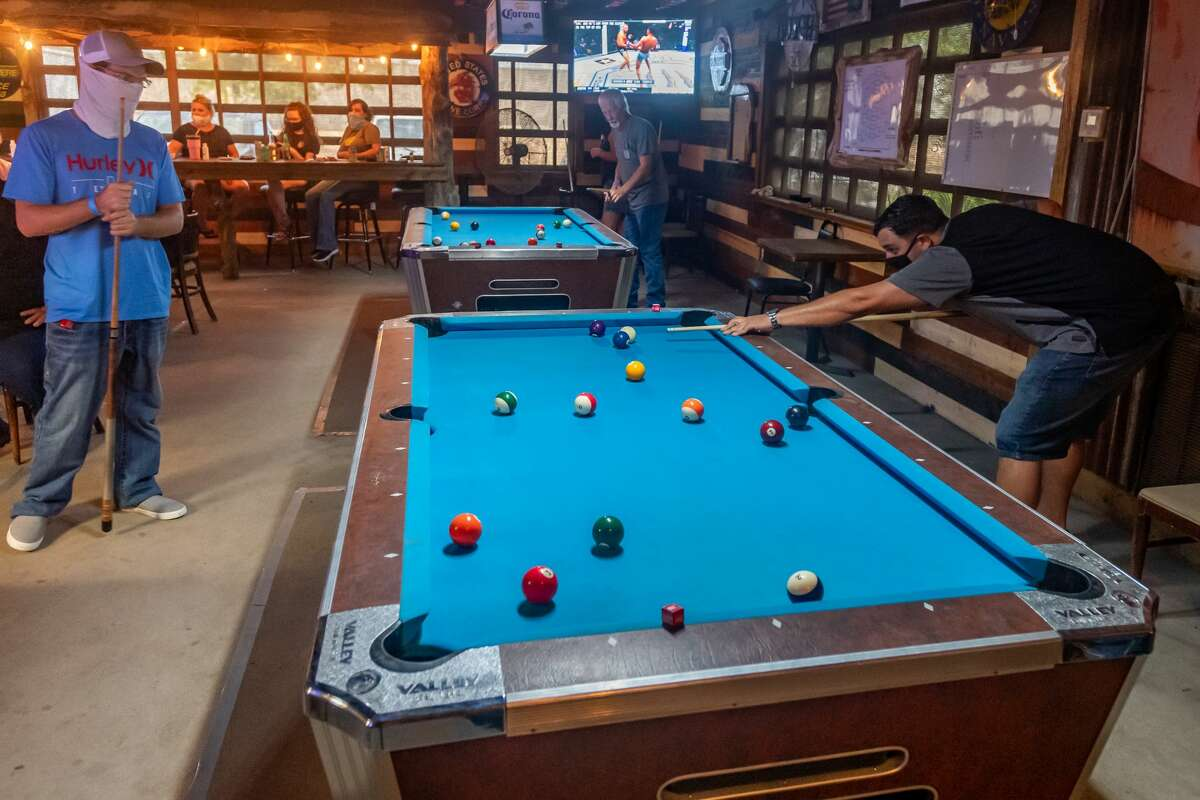 Josh Metz lines up a shot on one of the pool tables while Jared Y'Barbo waits for his turn. The Soggy Bottom Saloon in Beaumont joined more than 800 bars in the Freedom Fest State-Wide Unified 51%er Protest defying Governor Greg Abbot?•s executive order which shutdown bars. Photo made on July 25, 2020. Fran Ruchalski/The Enterprise