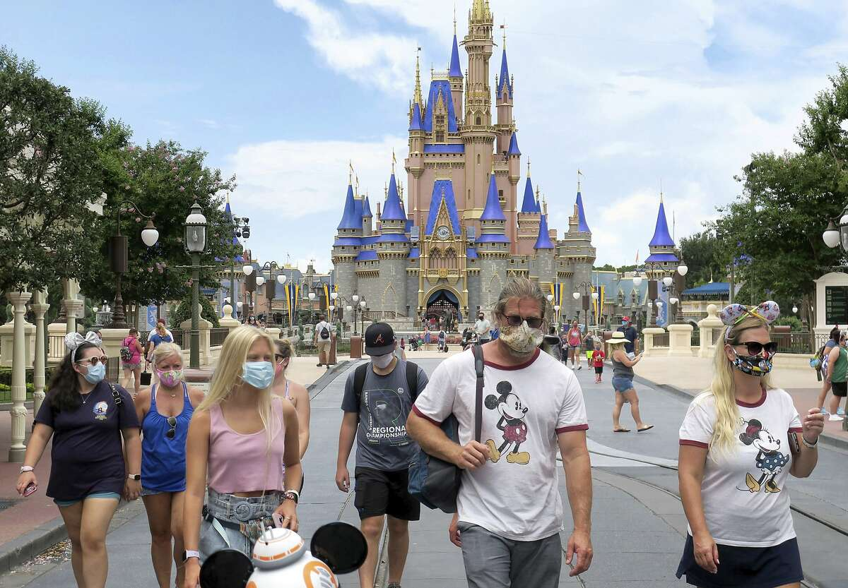 FILE - In this Saturday, July 11, 2020, file photo, guests wear masks as required to attend the official reopening day of the Magic Kingdom at Walt Disney World in Lake Buena Vista, Fla. (Joe Burbank/Orlando Sentinel via AP, File)