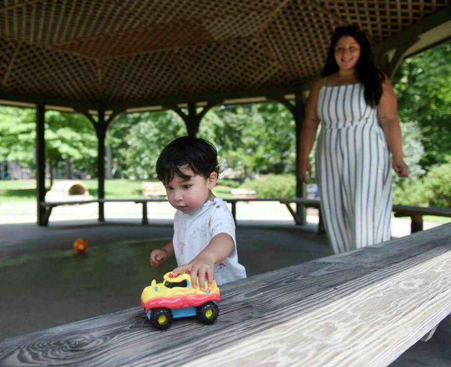 Greenwich's Leon Zion, 2, plays with his mother, Brenda Pardo, at the Bruce Park playground in Greenwich, Conn. Thursday, July 23, 2020. Greenwich playgrounds are reopen with precautions including mandatory social distancing, use of masks in areas where close contact with others is unavoidable, and recommended sanitizing of equipment before and after use. The two- to five-year-old playground has a maximum capacity of 20 people and the upper playground has a maximum capacity of 50 people. Photo: Tyler Sizemore / Hearst Connecticut Media / Greenwich Time