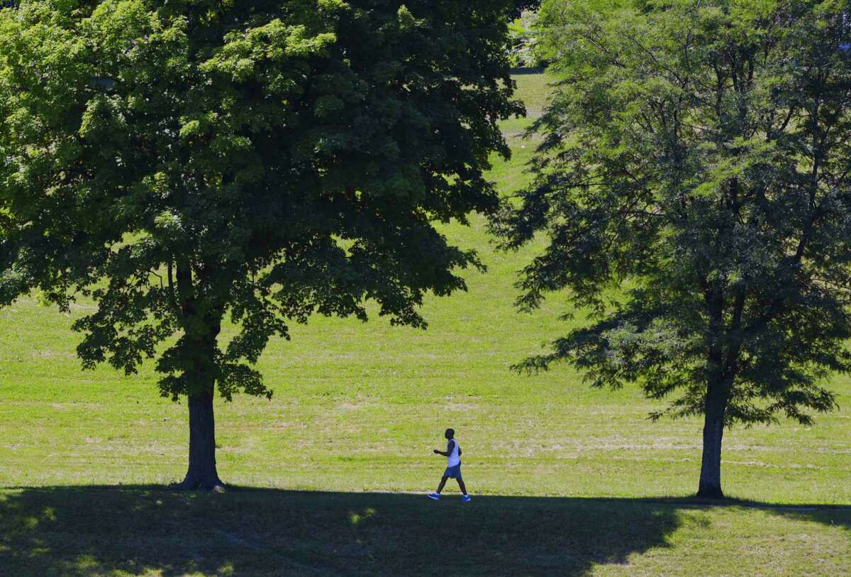 a man catches a brief break from the hot sun as he walk through Lincoln Park on Sunday, July 26, 2020, in Albany, N.Y. (Paul Buckowski/Times Union)