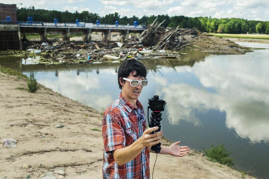 Freeland resident Jordan Mowbray stands in front of the Sanford dam Tuesday, July 21, 2020 as he films an introduction for the newest of his video updates in the aftermath of the flooding in May, which he posts to his YouTube channel. (Katy Kildee/kkildee@mdn.net) Photo: (Katy Kildee/kkildee@mdn.net)