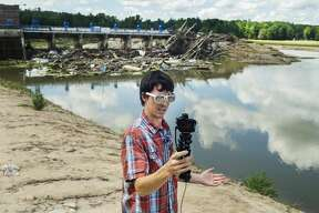 Freeland resident Jordan Mowbray stands in front of the Sanford dam Tuesday, July 21, 2020 as he films an introduction for the newest of his video updates in the aftermath of the flooding in May, which he posts to his YouTube channel. (Katy Kildee/kkildee@mdn.net)