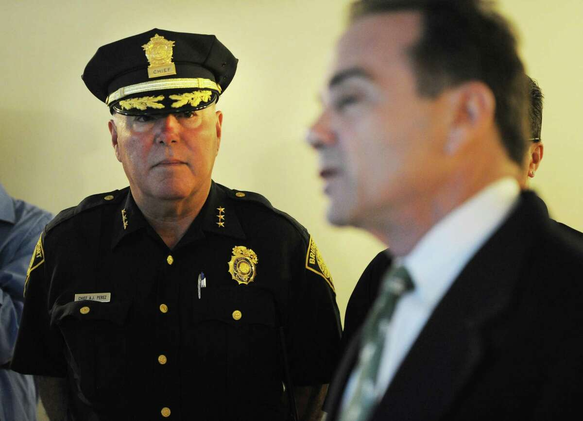Then-Bridgeport Police Chief A.J. Perez, left, listens as Mayor Joe Ganim speaks during a tour of the reactivated police post at P.T. Barnum Apartments in Bridgeport, Conn. on Thursday, August 17, 2017.