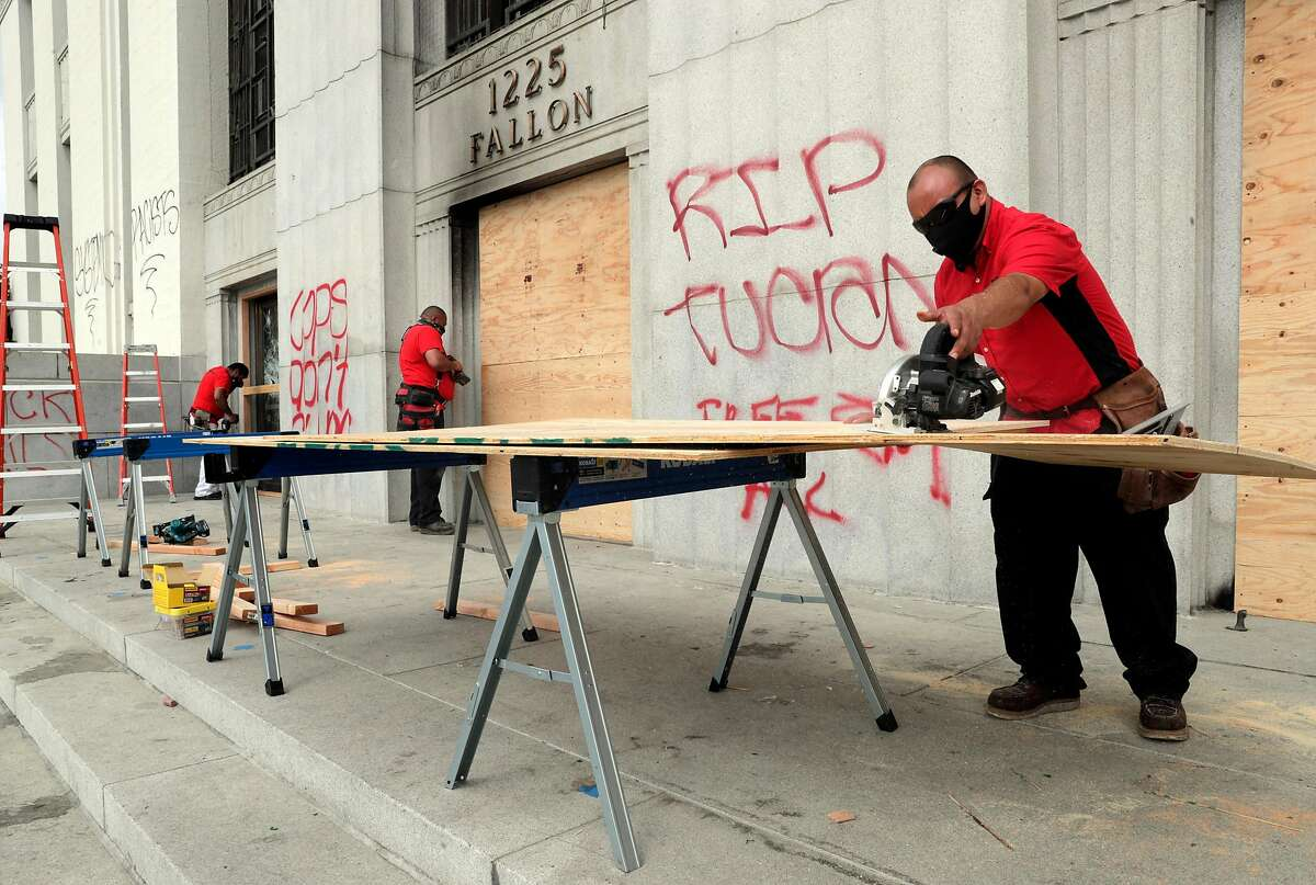 Workers for Belfor Property Restoration put up plywood over broken windows at the Alameda County Superior Courthouse that was damaged during an overnight protest in Oakland, Calif., on Sunday, July 26, 2020. The protest was done in solidarity with protesters in Portland who are facing federal law enforcement.