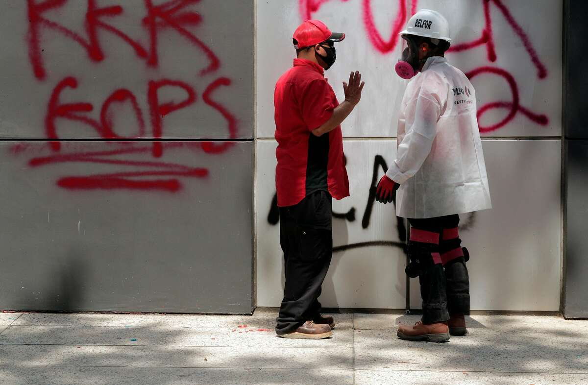 Workers for Belfor Property Restoration examine graffiti damage done at the Oakland Police Department during an overnight protest in Oakland, Calif., on Sunday, July 26, 2020. The protest was done in solidarity with protesters in Portland who are facing federal law enforcement.
