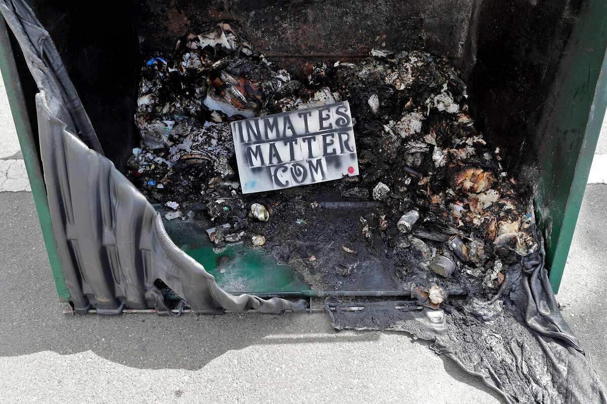 A sign sits in a burned out dumpster outside the Alameda County Superior Courthouse that was damaged during an overnight protest in Oakland, Calif., on Sunday, July 26, 2020. The protest was done in solidarity with protesters in Portland who are facing federal law enforcement.