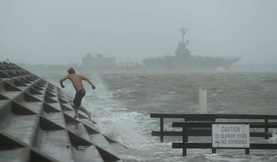 A man jumps from a wave as Hurricane Hanna begins to make landfall, Saturday, July 25, 2020, in Corpus Christi, Texas. The National Hurricane Center said Saturday morning that Hanna's maximum sustained winds had increased and that it was expected to make landfall Saturday afternoon or early evening.(AP Photo/Eric Gay) Photo: Eric Gay/AP / Copyright 2020 The Associated Press. All rights reserved.