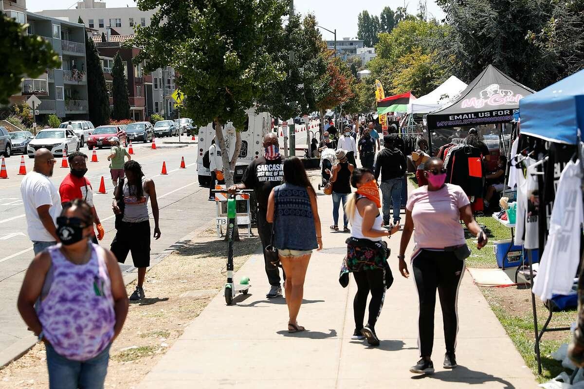 People stroll along Lakeshore Avenue at Lake Merritt in Oakland, Calif., on Sunday, July 26, 2020.