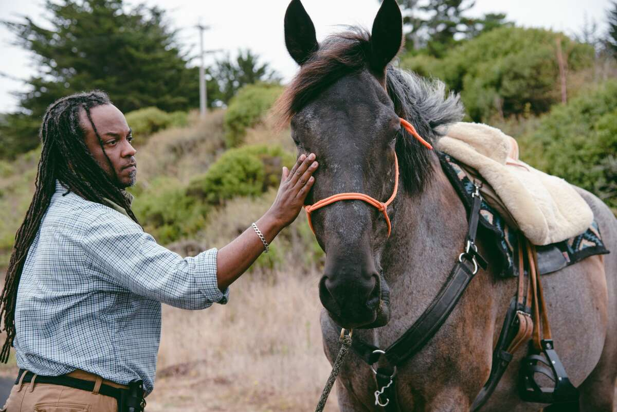 Concord resident Jason Ellis strokes Zevon, a horse belonging to friend Kestrel Rezos, while getting ready for the Heels Down Fists Up protest on July 26, 2020 in Sausalito. Ellis, who works as a massage therapist, became interested in horse riding after meeting Ms. Rezos through work last year.