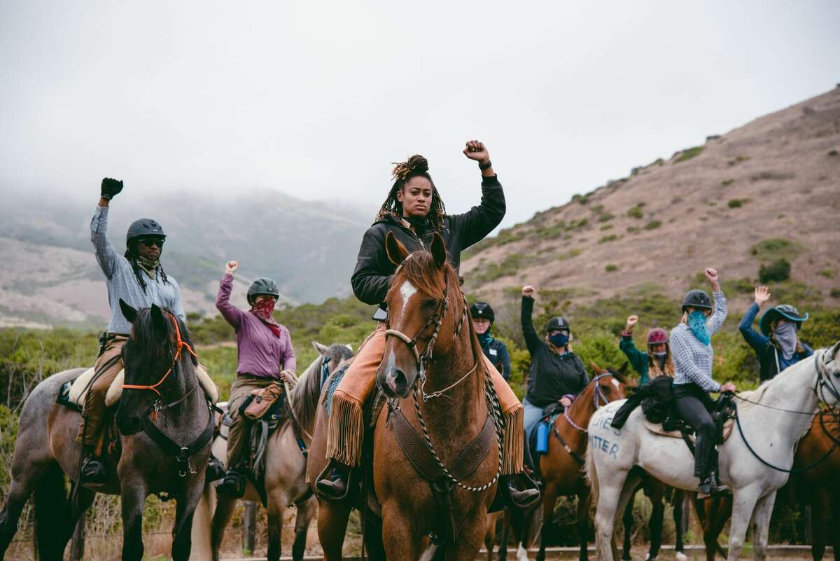 Brianna Noble leads a moment of silence with raised fists during the Heels Down Fists Up equestrian protest in solidarity with the Black Lives Matter movement on July 26, 2020 in Sausalito.