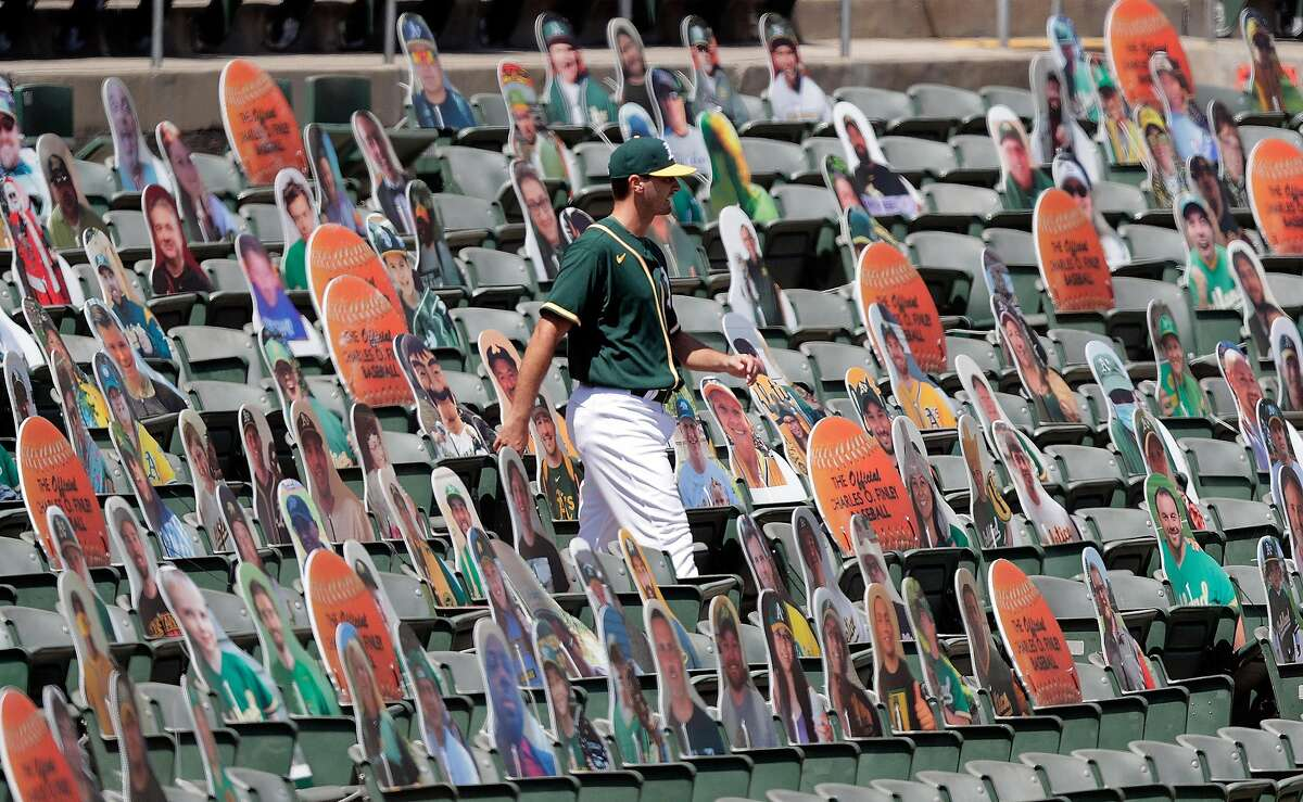 Burch Smith (46) walks among the cutouts as the Oakland Athletics played the Los Angeles Angels of Anaheim at the Coliseum in Oakland, Calif., on Sunday, July 26, 2020.