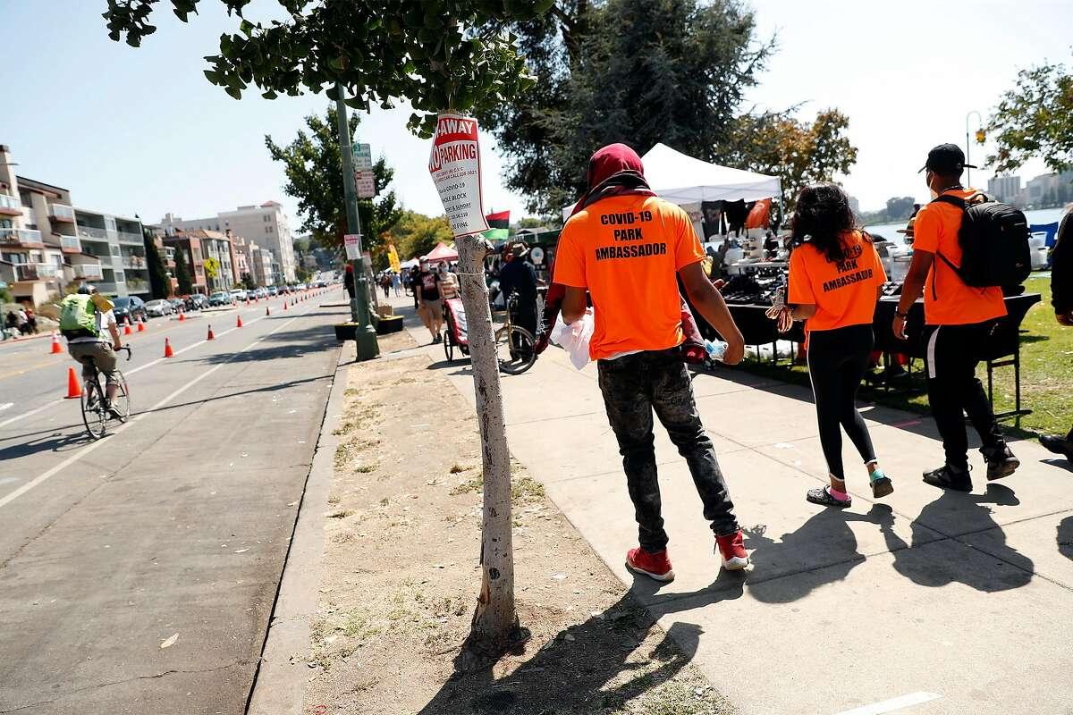 COVID-19 Park Ambassadors walk next to Lakeshore Avenue at Lake Merritt in Oakland, Calif., on Sunday, July 26, 2020.
