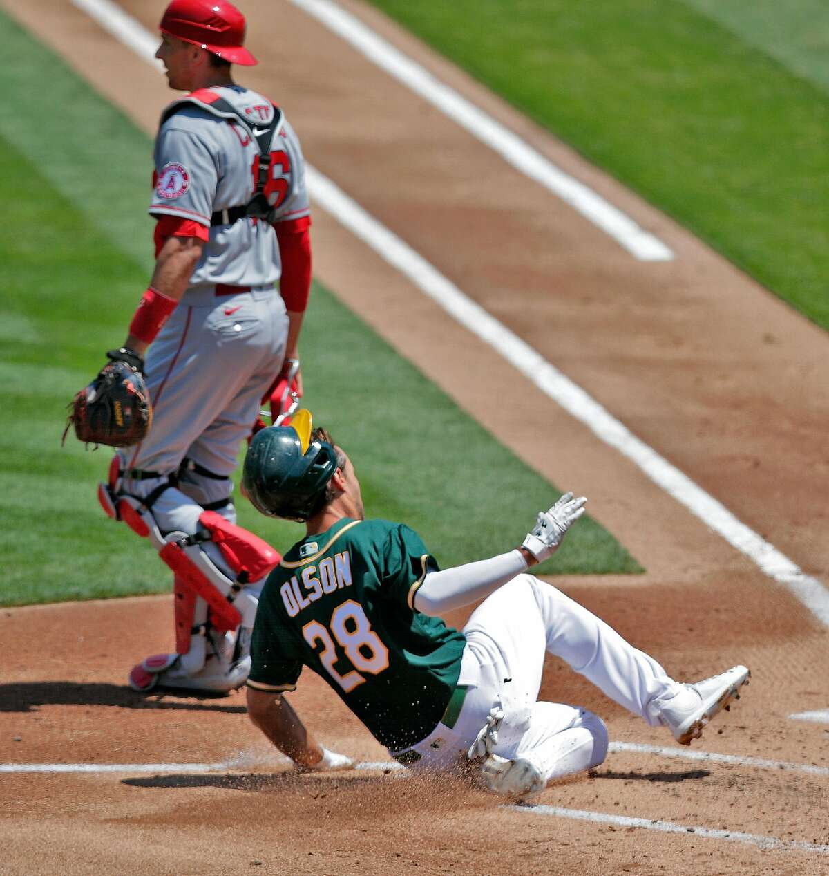 A's first baseman Matt Olson (28) scores safely ahead of the throw on a single by Robbie Grossman (8) in the first inning as the Oakland Athletics played the Los Angeles Angels of Anaheim at the Coliseum in Oakland, Calif., on Sunday, July 26, 2020.