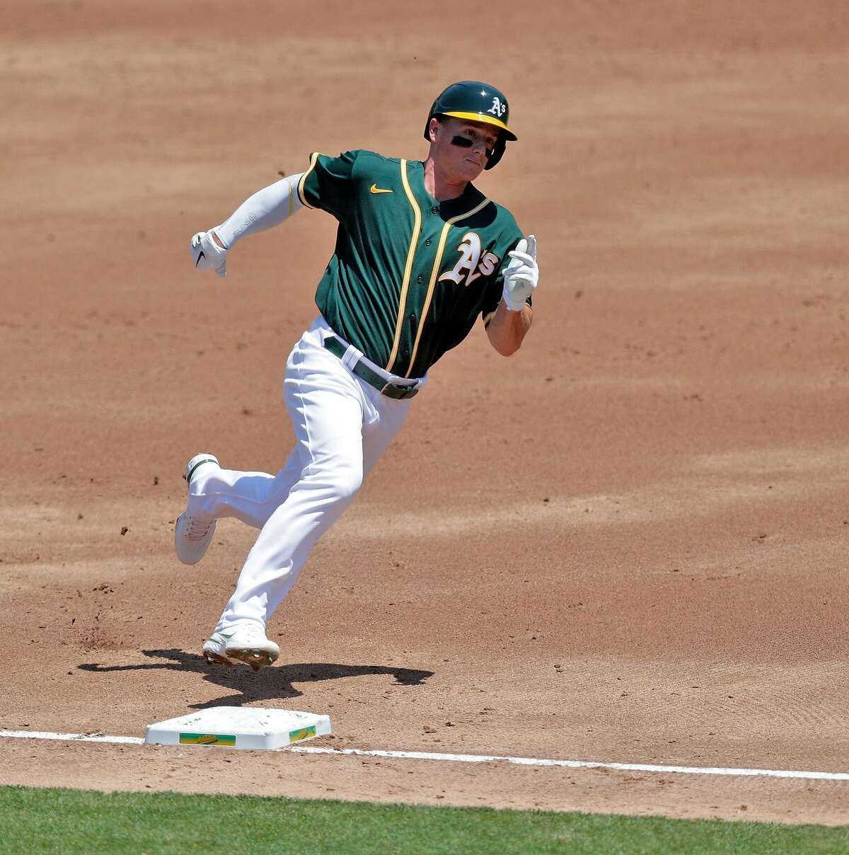 A's third baseman Matt Chapman (26) rounds third and scores on a Mark Canha (20) single in the first as the Oakland Athletics played the Los Angeles Angels of Anaheim at the Coliseum in Oakland, Calif., on Sunday, July 26, 2020.