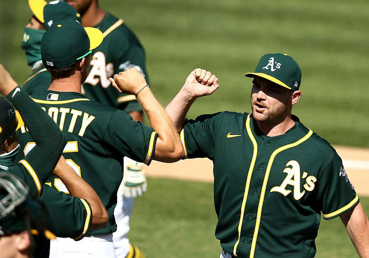 OAKLAND, CALIFORNIA - JULY 26: Liam Hendriks #16 and Stephen Piscotty #25 of the Oakland Athletics elbow bump after they beat the Los Angeles Angels at Oakland-Alameda County Coliseum on July 26, 2020 in Oakland, California. The 2020 season had been postponed since March due to the COVID-19 pandemic. (Photo by Ezra Shaw/Getty Images)