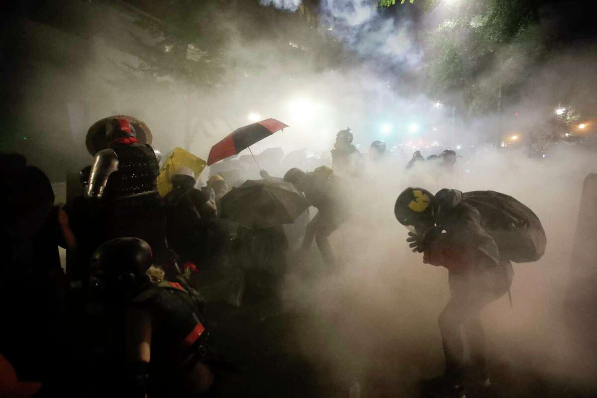 Federal officers launch tear gas at a group of demonstrators during a Black Lives Matter protest at the Mark O. Hatfield United States Courthouse Sunday, July 26, 2020, in Portland, Ore. (AP Photo/Marcio Jose Sanchez)