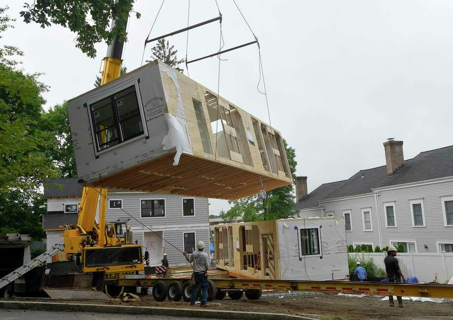 Workers from Westchester Modular Homes of Fairfield County and Fairfield Contractors LLC, prepared and install sections of a prefab house at 70 Seminary Road in New Canaan, Connecticut on July 23, 2020. Photo: Matthew Brown / Hearst Connecticut Media / Stamford Advocate