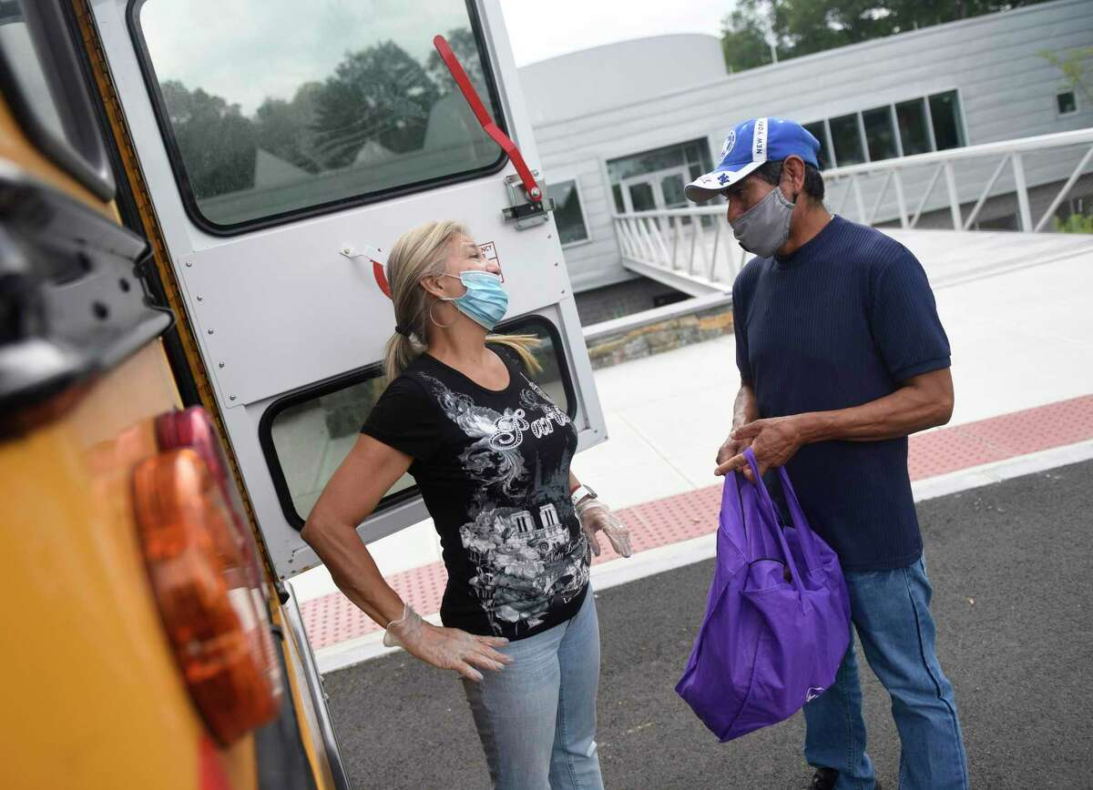 Food service worker Jeanette Romero distributes school lunches to Efrain Olivares outside New Lebanon School in the Byram section of Greenwich, Conn. Thursday, July 23, 2020. School breakfast and lunch distribution will continue through the summer and even into the fall for students who choose to stay at home.