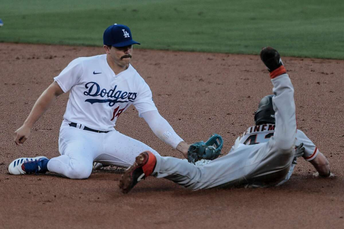 Los Angeles Dodgers left fielder Enrique Hernandez (14) is too late to tag San Francisco Giants catcher Tyler Heineman, who steals second base in the second inning on Sunday, July 26, 2020 at Dodger Stadium in Los Angeles. (Robert Gauthier/Los Angeles Times/TNS)