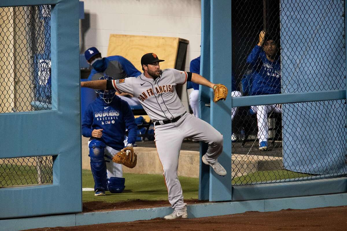 LOS ANGELES, CA - JULY 26: Los Angeles Dodgers bullpen door accidentally opens as San Francisco Giants left fielder Darin Ruf collides on the wall after catching a flay ball during a baseball game Sunday, July 26, 2020, in Los Angeles.