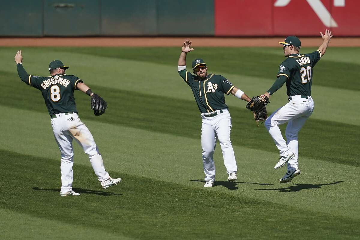 Oakland Athletics' Robbie Grossman, left, celebrates with Ramon Laureano and Mark Canha, right, after the Athletics defeated the Los Angeles Angels 6-4 in a baseball game in Oakland, Calif., Sunday, July 26, 2020. (AP Photo/Jeff Chiu)