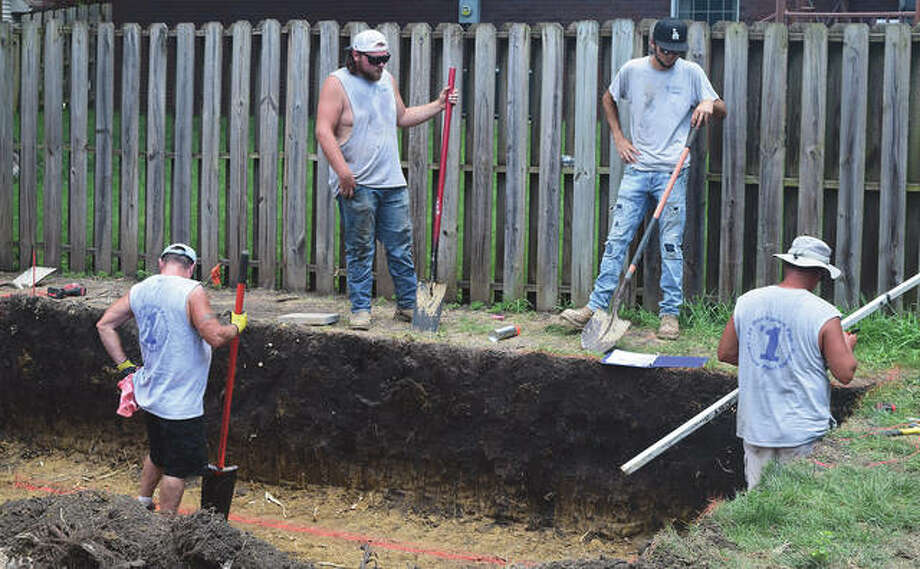 Mike Seymour (from left), Evan Schlieker, Matt Grimes and Peter Wilson of Leisure Pool Supply in Jacksonville install a pool in a backyard. Photo: Rochelle Eiselt | Journal-Courier